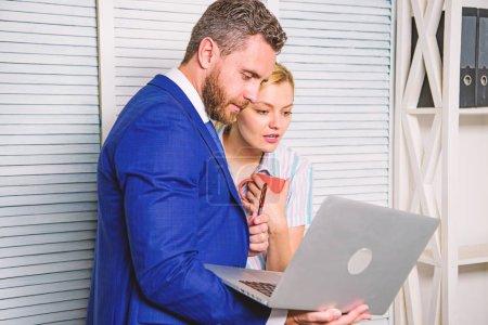Photo pour Patron et secrétaire ou assistant travaillent en équipe. Demandez l'avis d'un collègue. Bureau partenaire commercial afficher des statistiques de données d'information en ligne. Un homme d'affaires tient ordinateur portable surfer sur Internet avec un collègue . - image libre de droit