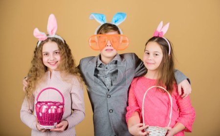 Photo for Spring in her basket. It is spring time. Children in rabbit bunny ears. Egg hunt. Family and sisterhood. Little girls and boy with busket. Spring holiday party. Happy easter. Enjoying springtime. - Royalty Free Image