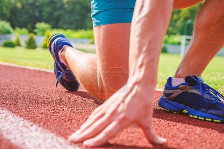 Photo for Starting point. Hand of sportsman on running track low start position. Runner ready to go close up. Ready steady go concept. At the beginning of great sport career. Hand touch track path close up. - Royalty Free Image