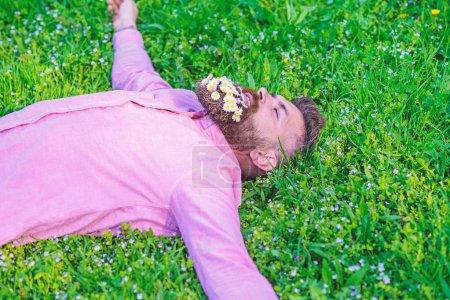 Photo pour Homme barbu avec des fleurs de marguerite dans la barbe posée sur prairie, fond d'herbe. Hipster avec bouquet de marguerites à la barbe relaxant. Unissez-vous au concept de la nature. Homme avec barbe sur le visage souriant profiter de la nature . - image libre de droit