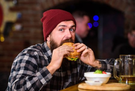 Photo for Brutal hipster bearded man sit at bar counter. High calorie food. Cheat meal. Delicious burger concept. Enjoy taste of fresh burger. Hipster hungry man eat burger. Man with beard eat burger menu. - Royalty Free Image