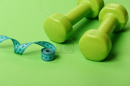Photo for Sports equipment and twisted cyan measuring tape. Barbells near long soft ruler. Dumbbells in bright green color isolated on green background, close up. Healthy lifestyle and workout concept. - Royalty Free Image
