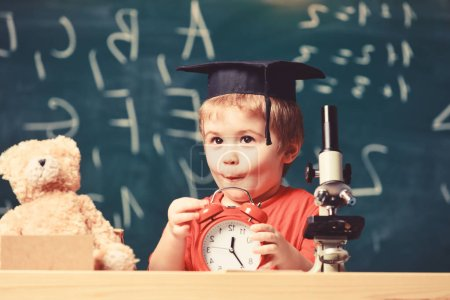 Photo for Child with alarm clock on table. Portrait of cute boy learning in classroom. Kid boy in academic cap near microscope, holds clock in classroom, chalkboard on background. Pupil waiting for school break - Royalty Free Image