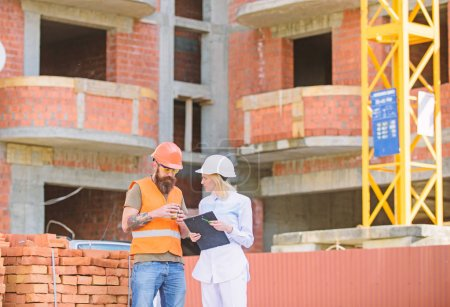 Photo for Relationships between construction clients and participants building industry. Woman engineer and builder communicate at construction site. Discussing plan. Construction team communication concept. - Royalty Free Image