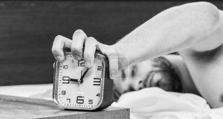 Photo pour Homme paresseux heureux se réveiller dans le lit s'élevant des mains le matin avec la sensation de fraîcheur détendue. Bel homme bâillement et étirant ses bras vers le haut. Homme lit détendue - image libre de droit