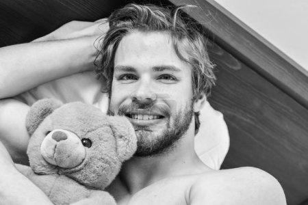 Photo pour Photo montrant un jeune homme s'étirant dans son lit. Homme ressentant des maux de dos dans le lit après avoir dormi. Homme sur le lit - image libre de droit