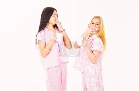 Photo pour Les filles boivent du thé ou du café le matin, isolées sur fond blanc. Concept de café du matin. Blonde et brune sur des visages endormis bâillant, tient des tasses avec du café. Soeurs ou meilleurs amis en pyjama . - image libre de droit