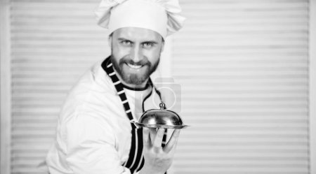 Photo pour Suivant sa recette préférée. Chef cuisinier en uniforme debout avec plat délicieux. Maître cuisinier de servir des repas au restaurant. Bel homme en chapeau tablier et cuire. Cuisine de grande classe. - image libre de droit