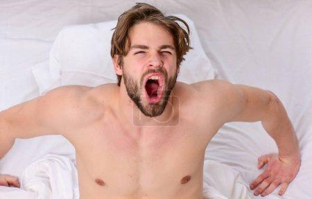Photo pour Homme paresseux heureux se réveiller dans le lit levant les mains le matin avec le sentiment frais détendu. L'homme s'étirant au lit. Réveil de jeune homme - image libre de droit