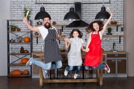 Photo pour Cuisine familiale. Intérieur. Une école culinaire. Bonne famille dans la cuisine. Mère et père avec une petite fille. Petite fille avec des parents dans le tablier. Chef cuisinier père, mère et enfant. Jour de famille - image libre de droit