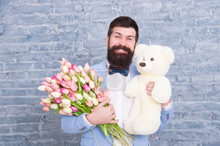 Photo for Romantic gift. Macho getting ready romantic date. Man wear blue tuxedo bow tie hold flowers bouquet. International womens day. Surprise will melt her heart. Romantic man with flowers and teddy bear. - Royalty Free Image