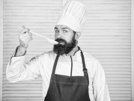 Photo pour Cuisiner comme profession professionnelle. Le chef barbu de hipster retiennent la cuillère en bois. Cuisine et concept de cuisine. Essayons le goût. Ajouter quelques épices. Homme avec la barbe dans le chapeau de cuisinier et les outils de cuisson de prise de tablier. - image libre de droit