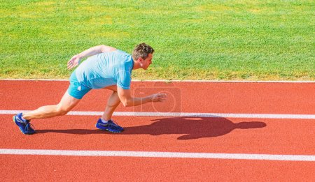 Photo for Boost speed concept. Man athlete runner push off starting position stadium path sunny day. Runner sprint race at stadium. Runner captured in motion just after start of race. How to start running. - Royalty Free Image