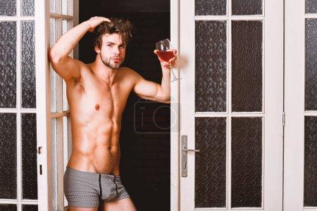 Photo pour Concept de l'amant sexy. Peau lisse de Guy posant séduisant. Grande soirée de début. Homme à boire du vin torse sexy. Sexy séduisante macho cheveux ébouriffés qui sort par la porte de la chambre. Corps sexy baccalauréat. - image libre de droit