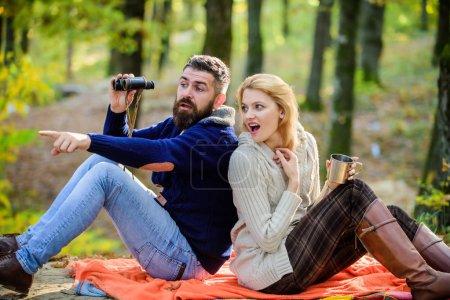 sauvage en plein air. couple amoureux se détendre dans la forêt d'automne avec du thé ou du café. camping et randonnée. surprise fille boire vin chaud. homme barbu montre choquée avec des jumelles. Humeur printanière. Pique-nique familial