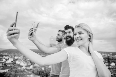 Photo pour Nous sommes tous des individus. Les gens aiment selfie tir sur la nature. Meilleurs amis prenant selfie avec téléphone de la caméra. Sexy fille et les hommes tenant smartphones dans les mains. Partager des selfies sur les réseaux sociaux . - image libre de droit
