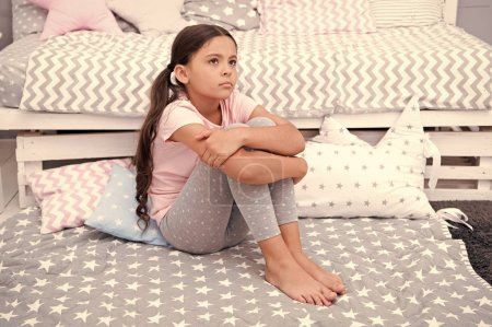 Photo for Sad concept. Sad little girl. Sad child sit on bed. Sad kid in bedroom at home. I want to play. - Royalty Free Image