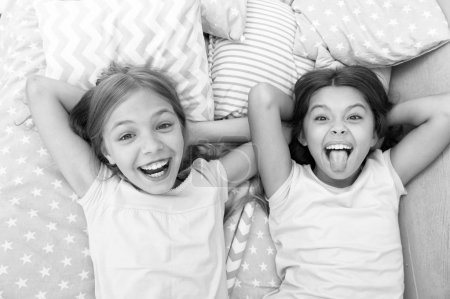 Photo for Having fun with best friend. Children playful cheerful mood having fun together. Pajama party and friendship. Sisters happy small kids relaxing in bedroom. Friendship of small girls. Leisure and fun. - Royalty Free Image