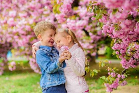 Photo pour Tendres sentiments d'amour. La petite fille apprécient des fleurs de source. En lui donnant toutes les fleurs. La surprendre. Gosses appréciant la fleur rose de cerise. Des bébés romantiques. Gosses de couples sur des fleurs de fond d'arbre de sakura. - image libre de droit