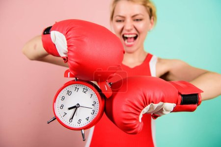Photo for Improve yourself. Overcome harmful habits. Time for training. Get used to personal regime. Girl athlete boxing gloves and alarm clock. Sport lifestyle and healthy regime. Habits and regime concept. - Royalty Free Image