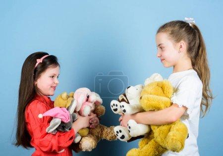 Foto de Relajarse juntos. patio de recreo en el jardín de infantes. hermanitas niñas jugando en la sala de juegos. niñas pequeñas con juguetes de oso blando. infancia feliz. Artesanal. costura y artesanías de bricolaje. juguetería. día de los niños. - Imagen libre de derechos