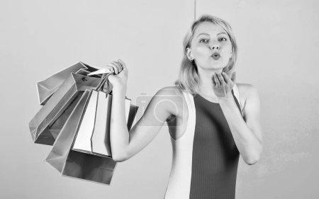 Photo pour Achète tout ce que tu veux. Fille satisfaite du shopping. Conseils pour faire des ventes avec succès. Fille profiter du shopping ou vient d'obtenir des cadeaux d'anniversaire. Femme robe rouge tenir tas de sacs à provisions fond bleu rose. - image libre de droit