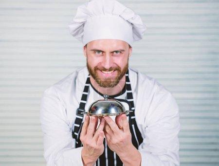 Photo pour Chef cuisinier. Bel homme en chapeau tablier et cuire. Chef cuisinier en uniforme debout avec plat délicieux. Maître cuisinier de servir des repas au restaurant. Restaurant gastronomique accueillant. - image libre de droit