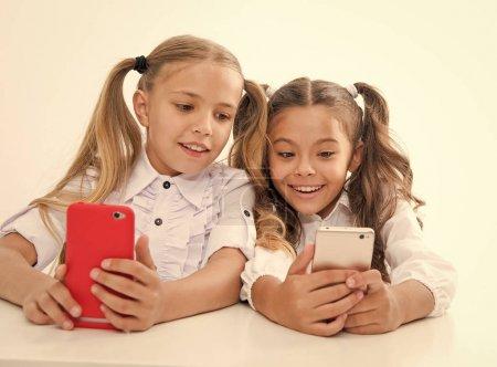Photo pour Formation en ligne pour les enfants numériques avec des visages heureux. éducation en ligne. childgren heureux avec des appareils numériques - smartphones. Nous vivons dans l'ère du numérique. - image libre de droit