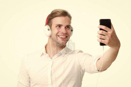 Photo pour Im en ligne. Fan de musique. Bel homme écouter de la musique au casque. Homme d'affaires lire ebook business en ligne. Ebook détient beaucoup c'est important pour moi. - image libre de droit