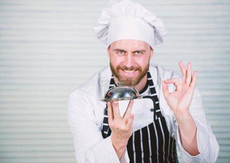 Photo pour Chef cuisinier gesticulant signe OK. Maître cuisinier de servir des repas au restaurant. Bel homme en chapeau tablier et cuire. Chef cuisinier en uniforme debout avec plat délicieux. Notre restaurant est idéal pour tous les goûts. - image libre de droit