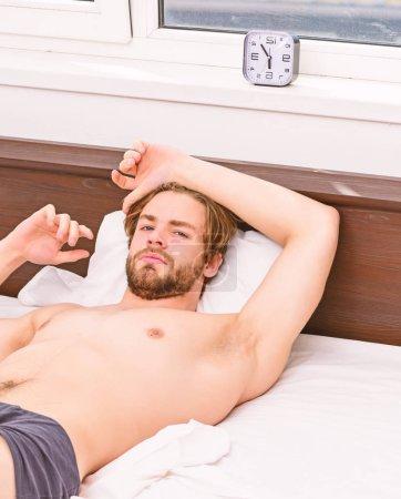 Photo pour Un jeune homme se réveille dans son lit et étire les bras. Un bel homme bâillant et étirant les bras. Homme bâillant en se réveillant - image libre de droit