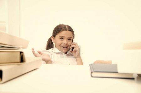 Photo pour Utilisation des nouvelles technologies de communication dans l'enseignement scolaire. Petite fille parlant sur téléphone portable en leçon. Petite écolière ayant un coup de fil. Écolière développant des compétences en communication. Être sur un appel . - image libre de droit