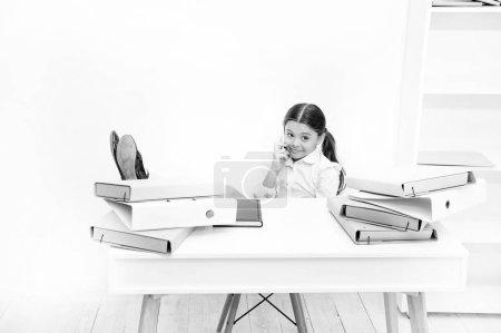 Photo pour Une fille bavarde. Petite fille qui parle sur son portable en leçon. Petite écolière ayant un coup de fil. Écolière développant des compétences en communication. Utilisation des nouvelles technologies de communication dans l'enseignement scolaire . - image libre de droit