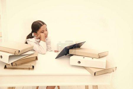 Photo pour Lecture lui fait s'ennuient. Élève adorable développer des compétences en lecture. Écolière lecture livre scolaire au comptoir. Fillette lisant le livre de cours à l'école. Petit enfant de l'école ont leçon de littérature. - image libre de droit