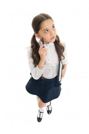 Photo pour Et si... Un gamin en uniforme qui fait ses devoirs. Les vêtements d'école de fille tiennent le livre et le stylo. Fille mignonne noter des notes d'idée. Des notes à retenir. Rédigez un essai ou des notes. Horaire personnel. Prendre des notes . - image libre de droit