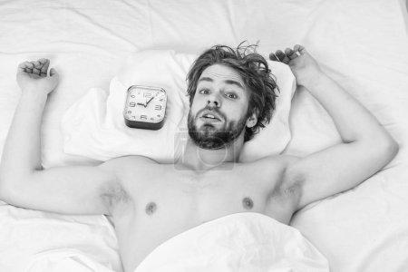 Photo pour Un bel homme bâillant et étirant les bras. Un jeune homme se réveille dans son lit et étire les bras. Réveillez-vous le matin - image libre de droit