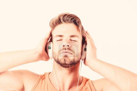 Photo pour Ebook et l'éducation en ligne. l'éducation musicale. homme musclé sexy écouter ebook. homme dans des écouteurs isolés sur le blanc. e livre. l'étude de l'homme mal rasé en ligne. Apprécier sa musique préférée. - image libre de droit