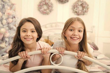 Photo pour Temps de partager tous les rires et la joie. Heureux, les enfants ont l'esprit de Noël. Petites filles dans son lit le soir de Noël. Petits enfants dans la chambre à coucher avec arbre de Noël. Traditions de Noël de l'enfance. - image libre de droit