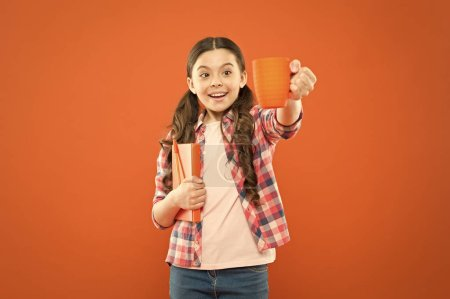Photo for Help yourself. Cute schoolgirl enjoying school break on orange background. Little girl having tea break. Small child holding book and cup at meal break. Its break time. - Royalty Free Image