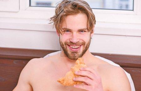Photo pour Homme barbu beau mec qui mange le petit déjeuner au lit. Un bel homme buvant du café du matin dans le lit. Beau jeune homme profitant de sa tasse de café du matin couché dans le lit chambre d'hôtel heureux souriant - image libre de droit