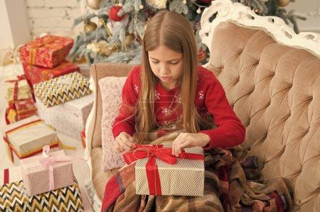 Photo pour Enroulant vers le haut très bien. Petite fille avec boîte-cadeau. Enfant heureux célébrer Noël et nouvel an. Fille enfant se préparent pour la fête de boxing day. Boxing day est le jour après Noël. Bonne année. - image libre de droit