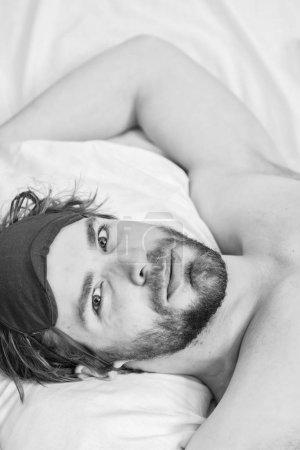 Photo pour Homme ressentant des maux de dos dans le lit après avoir dormi. Homme paresseux heureux de se réveiller dans le lit levant les mains le matin avec une sensation de fraîcheur détendue. Homme endormi se réveillant tôt après avoir entendu le signal d'alarme - image libre de droit