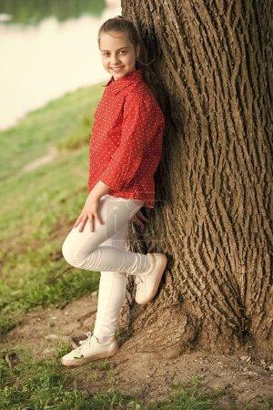 Photo pour Profiter des vacances d'été. Petite fille se relaxant à l'arbre le jour d'été. Adorable enfant aux longs cheveux blonds dans un style décontracté sur un paysage d'été. Petit enfant portant une tenue d'été mode . - image libre de droit