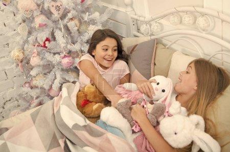 Photo pour Jolly et drôle. Petits enfants profiter de Noël. Petits enfants sont amuser de Noël. Petites filles disputent des jouets. Actives petits enfants dans son lit à l'arbre de Noël. Jeux de l'enfance sur Noël et nouvel an. - image libre de droit