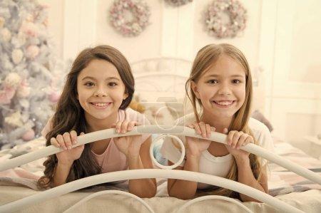 Photo pour Noël est passer du temps avec des amis. Petites filles dans son lit le soir de Noël. Heureux, les enfants ont l'esprit de Noël. Petits enfants dans chambre avec arbre de nouvel an. Noël enfance - image libre de droit