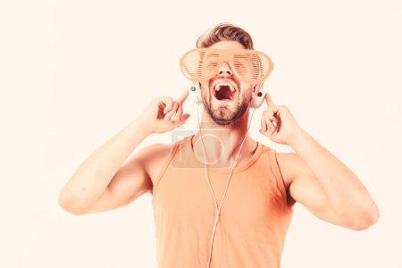 Photo pour Homme émotif avec la musique d'écoute d'écouteurs. homme mal rasé écouter de la musique en casque. l'homme musculaire sexy écoutent la musique de sport. homme dans des écouteurs isolés sur le blanc. - image libre de droit