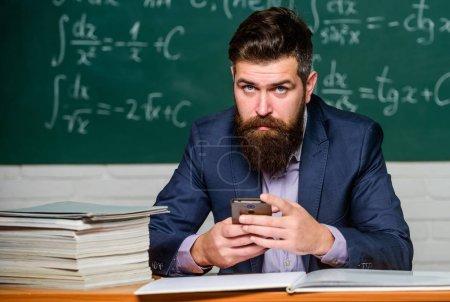 Photo pour Rencontrez l'homme dirigeant l'éducation en ligne. L'homme enseignant utilise les nouvelles technologies à l'école. Homme d'affaires acheter en ligne. Marketing numérique. Homme barbu tenir téléphone mobile . - image libre de droit