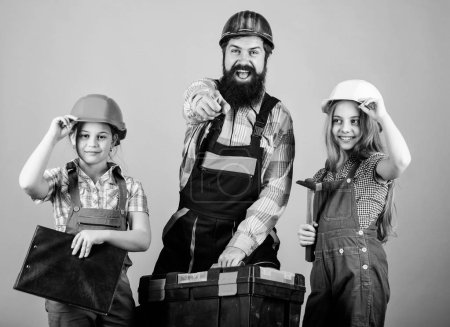 Father and daughter in workshop. Family teamwork. Repair. Repairman in uniform. Engineer. Bearded man with little girls. construction worker assistant. Builder or carpenter. Cheerful mechanic