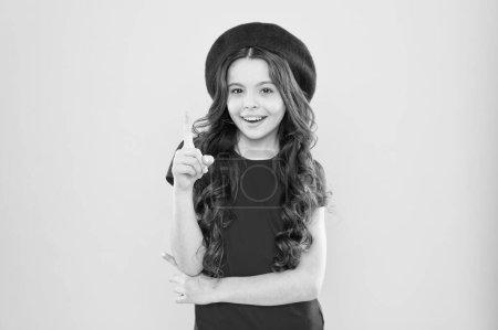 Photo pour Inspiration de designer. Petite fille au chapeau à la française. enfance. salon de coiffure. enfant parisien sur fond jaune. mode d'été et beauté. fille heureuse avec de longs cheveux bouclés en béret. - image libre de droit