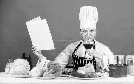 Photo pour Essayer une recette de dîner sain. Jolie femme affichant le livre de recette dans la cuisine. Femme au foyer recherchant la recette de cuisine dans le livre de cuisine. Cuisinier professionnel cuisinant le dîner végétarien selon la recette. - image libre de droit
